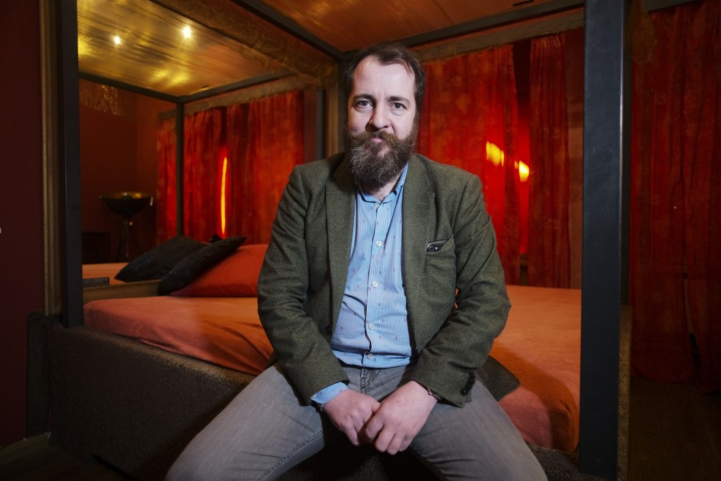 Aurel Johannes Marx sits on a bed in his three room brothel 'Lankwitzer 7' as he poses for photo after and interview with the Associated Press in Berl...