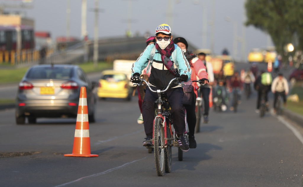Commuters, wearing protective masks, ride their bicycles in Bogota, Colombia, Tuesday, March 17, 2020. Officials in Colombia's capital have expanded b...