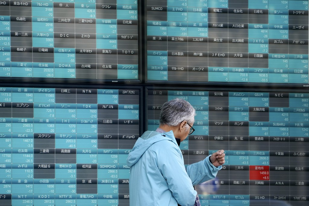 A man walks past an electronic stock board showing Japan's Nikkei 225 index at a securities firm in Tokyo Tuesday, March 17, 2020. Shares have fallen ...