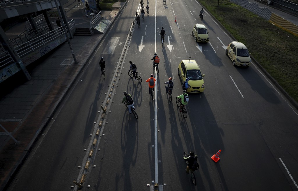 Commuters ride their bicycles in Bogota, Colombia, Tuesday, March 17, 2020. Officials in Colombia's capital have expanded bike routes, encouraging peo...