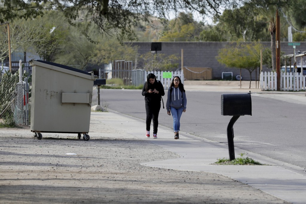 Children walk along a side street Friday, Jan. 24, 2020 in Guadalupe, Ariz. Founded by Yaqui Indian refugees from Mexico more than a century ago, Guad...