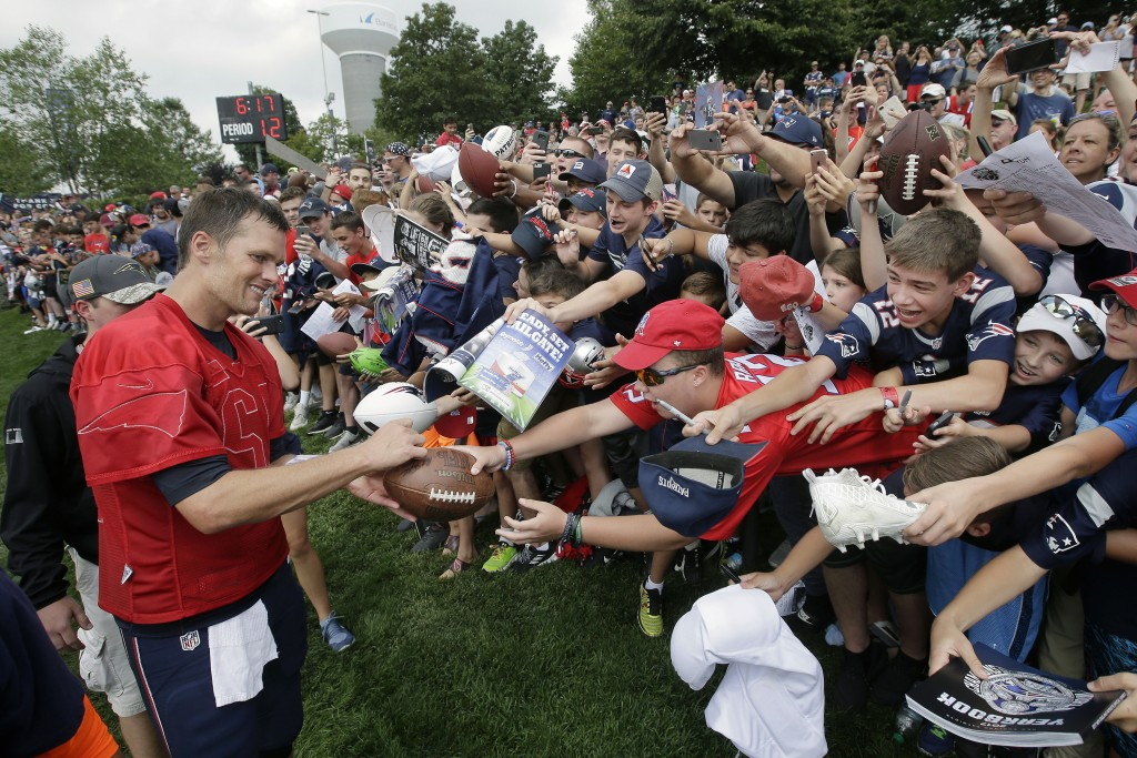 FILE - In this Aug. 3, 2017, file photo, New England Patriots' Tom Brady, left, signs autographs for fans at NFL football training camp in Foxborough,...