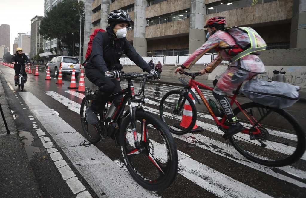 Commuters wearing protective masks ride their bicycles in Bogota, Colombia, Monday, March 16, 2020. Officials in Colombia's capital have expanded bike...