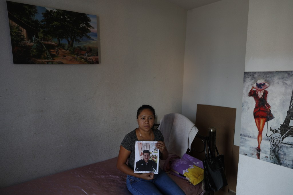 In this Feb. 13, 2020 photo, Alondra Mora holds a picture of her husband, Miguel Flores Lopez, 38, who disappeared Jan. 10, as she sits on the single ...
