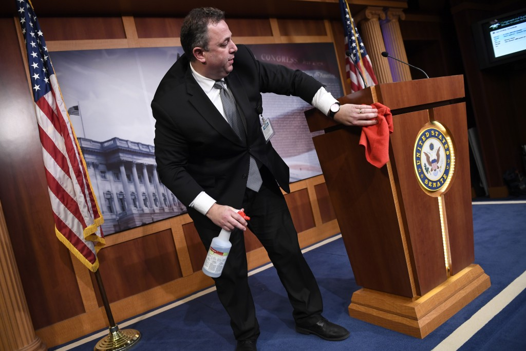 Mike Mastrian, director of the Senate Radio and Television Gallery, cleans down the podium before a news conference with Senate Minority Leader Sen. C...