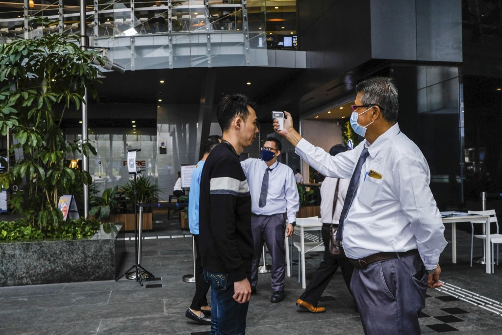 In this March 16, 2020, photo, a man scans a visitor's forehead to check his temperature before entering the Asia Square Tower in Singapore. As the vi...