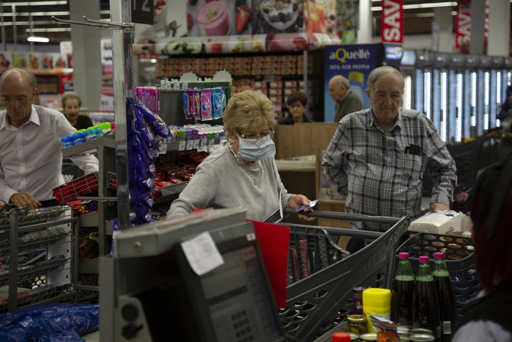 Elderly customers line at the checkout point in a Johannesburg supermarket Wednesday, March 18, 2020, amid panic-buying due to the new coronavirus out...