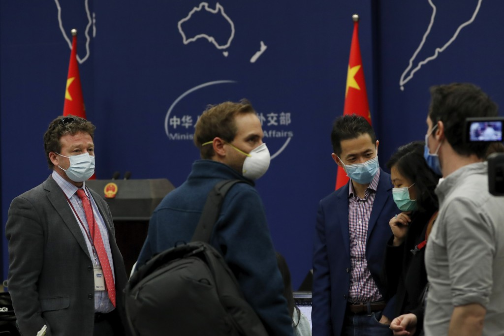 The New York Times Beijing based correspondent Steven Lee Myers, left, chats with other foreign journalists after attending a daily briefing by Chines...