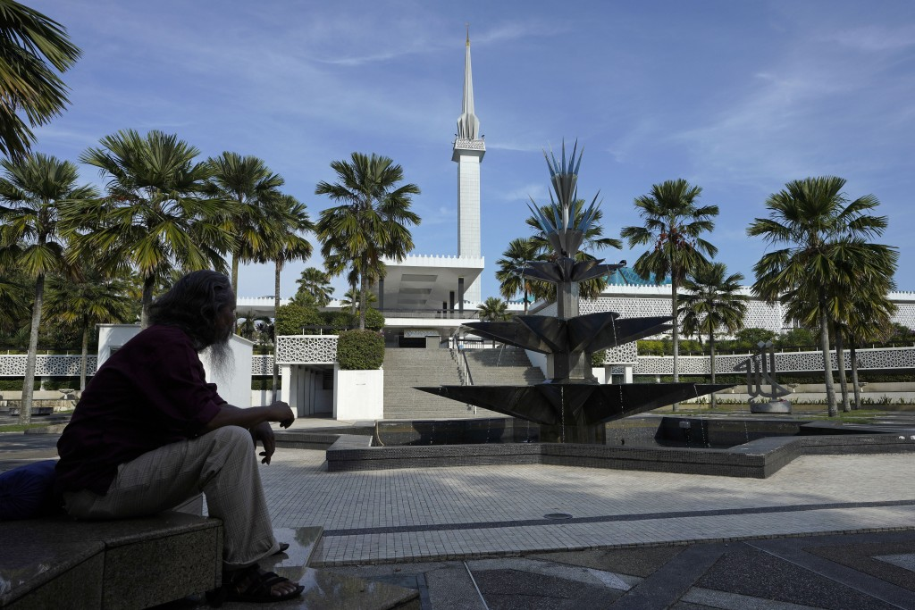 A men sit in front of National Mosque in Kuala Lumpur, Malaysia, Wednesday, March 18, 2020. Malaysian government issued a movement order to the public...