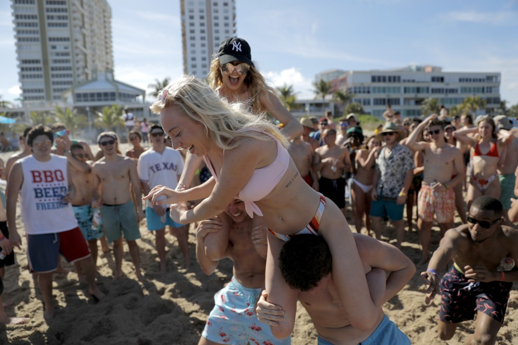 Cece Guida, 19, top, of New York City, pushes on Sam Reddick, 20, of Evansville, Ind., as spring break revelers look on during a game of chicken fight...