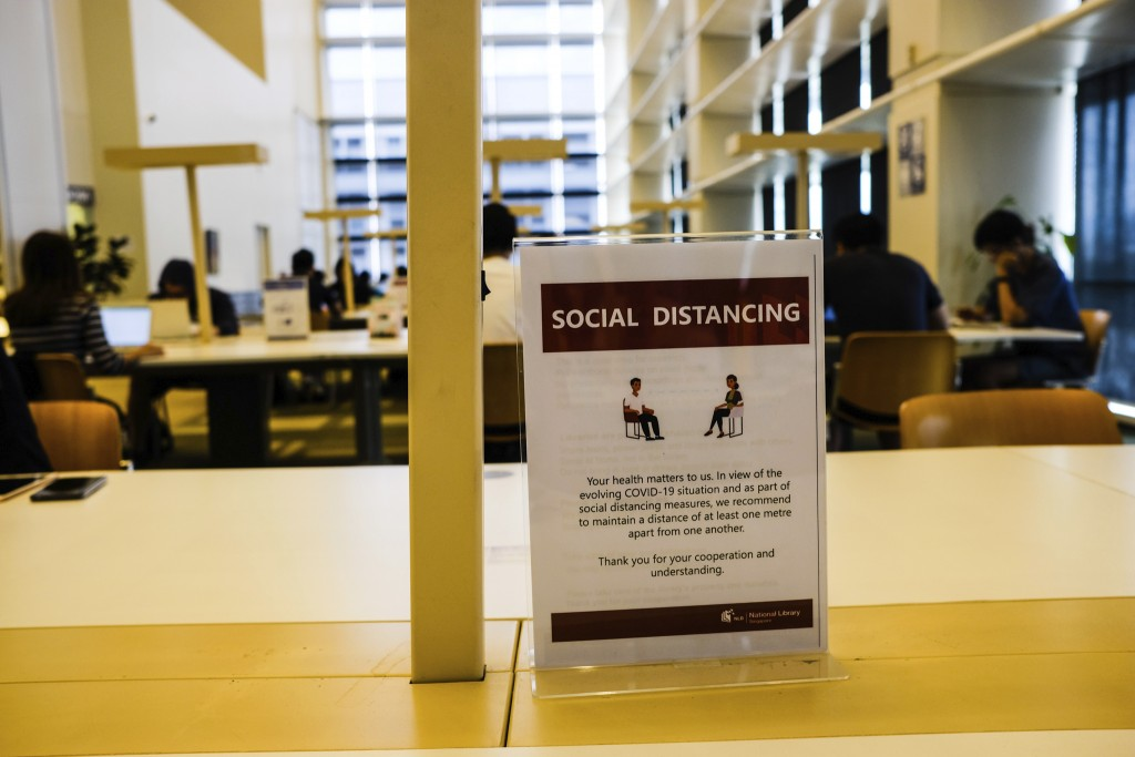 In this March 16, 2020, photo, a sign about social distancing is placed on a table at the National Library in Singapore. As the virus outbreak spreads...