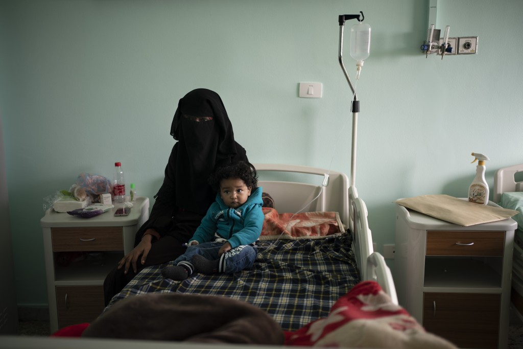 FILE - In this Feb. 27, 2020 file photo, Yazan, 1, sits with his mother before his heart surgery at the Tajoura National Heart Center in Tripoli, Liby...