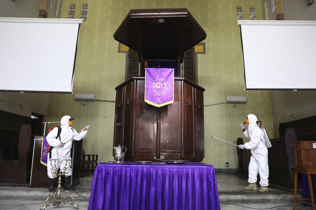 Workers of Disaster Mitigation Agency spray disinfectant inside a church amid fears of the new coronavirus outbreak in Surabaya, East Java, Indonesia,...
