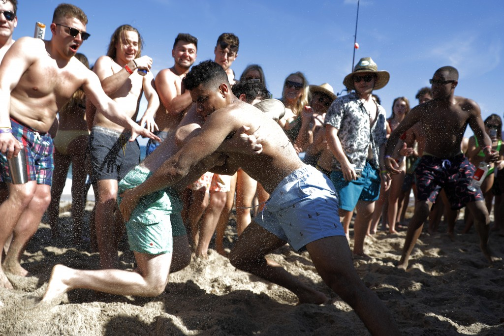 Two men wrestle each other as spring break revelers look on during a contest on the beach, Tuesday, March 17, 2020, in Pompano Beach, Fla. As a respon...