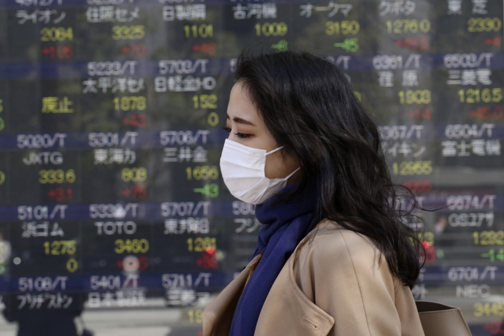 A woman walks by an electronic stock board of a securities firm in Tokyo, Wednesday, March 18, 2020. Major Asian stock markets are higher after Wall S...