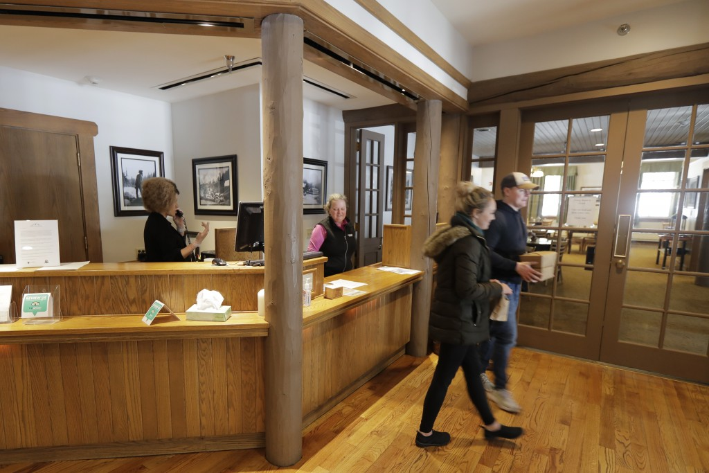 Visitors to the National Park Inn at Longmire walk away with a to-go order of food from the inn's restaurant at Mount Rainier National Park, Wednesday...