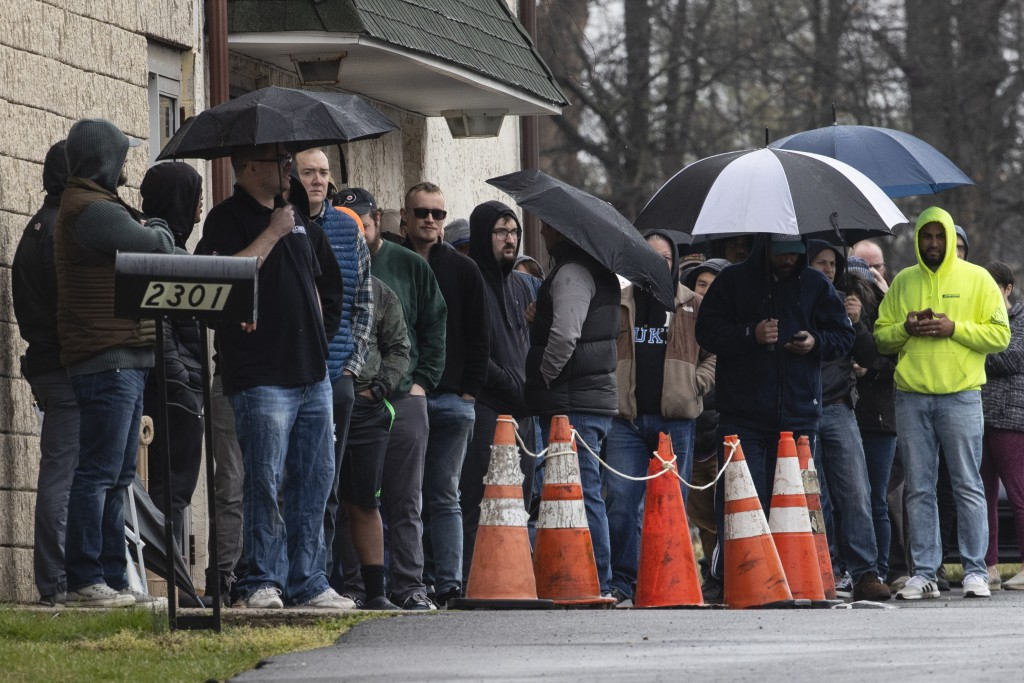 People wait in line to enter gun seller Tanner's Sports Center in Jamison, Pa., Tuesday, March 17, 2020. Pennsylvania's state-run background check sys...