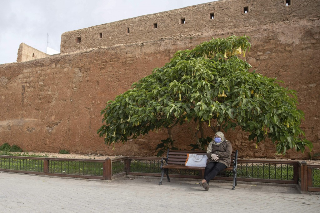 A woman wearing a face mask takes a rest by the walls of the old Medina of Rabat, Morocco, Wednesday, March 18, 2020. For most people, the new coronav...