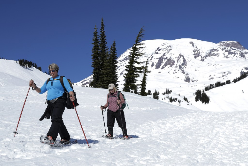 Danielle Kiechler, left, and Cathi Gouveia snowshoe above Paradise at Mount Rainier National Park, Wednesday, March 18, 2020, in Washington state. Mos...