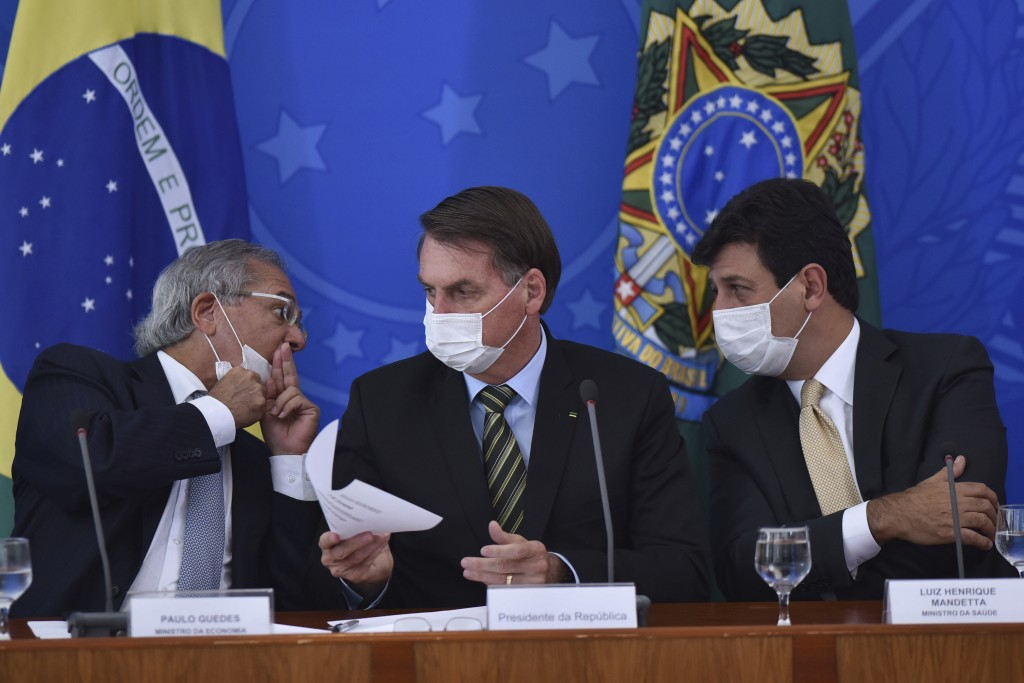 Wearing masks, Brazil's President Jair Bolsonaro, center, holds a piece of paper as Economy Minister Paulo Guedes, left, speaks to Health Minister Lui...