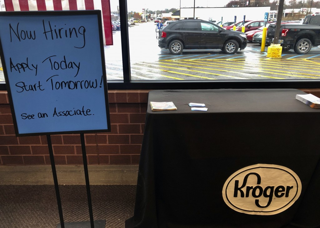 FILE - In this March 18, 2020 file photo, a sign encouraging job seekers to apply stands in a suburban Cincinnati Kroger store.  Kroger Co. joins a gr...