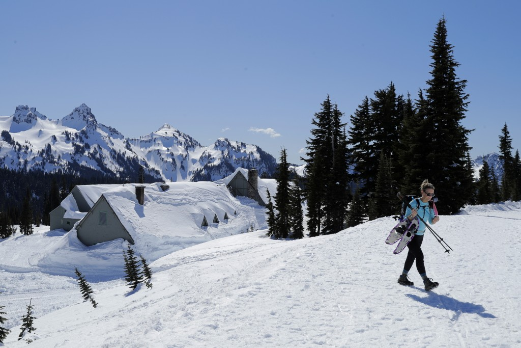 A snowshoer walks near the Paradise Inn at Mount Rainier, which is closed for the winter, at Mount Rainier National Park, Wednesday, March 18, 2020, i...