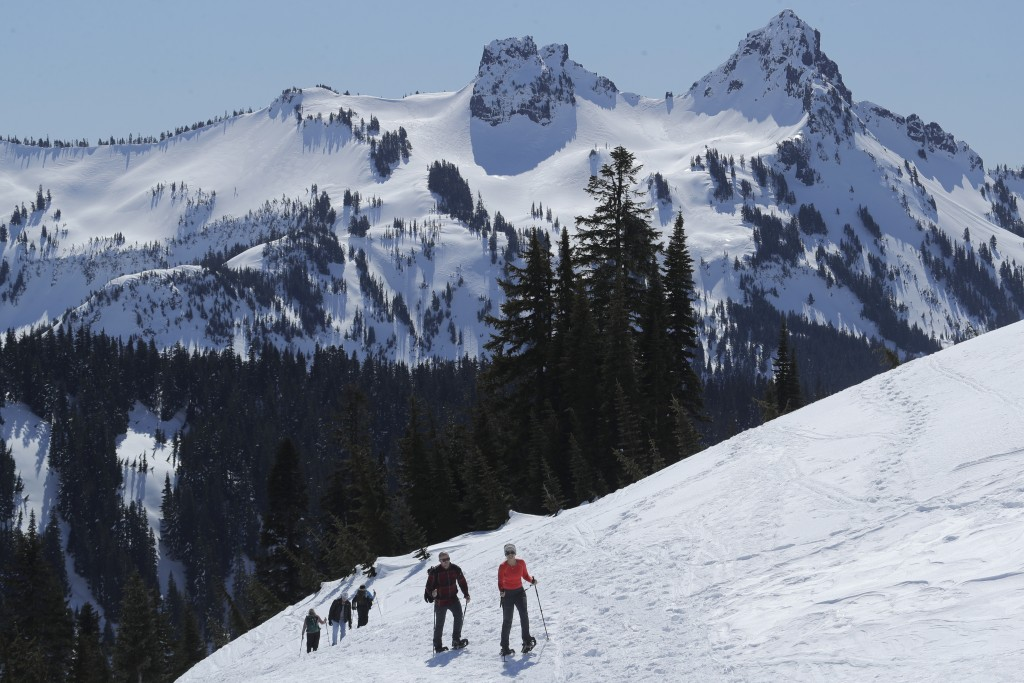 Snowshoers head up a slope above Paradise at Mount Rainier National Park, Wednesday, March 18, 2020, in Washington state. Most national parks are rema...