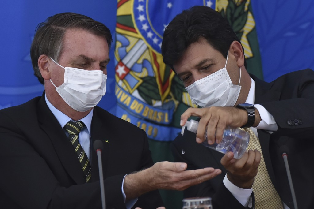 Wearing masks, Brazil's Health Minister Luiz Henrique Mandetta, right, applies alcohol gel on hands of President Jair Bolsonaro's hands during a press...