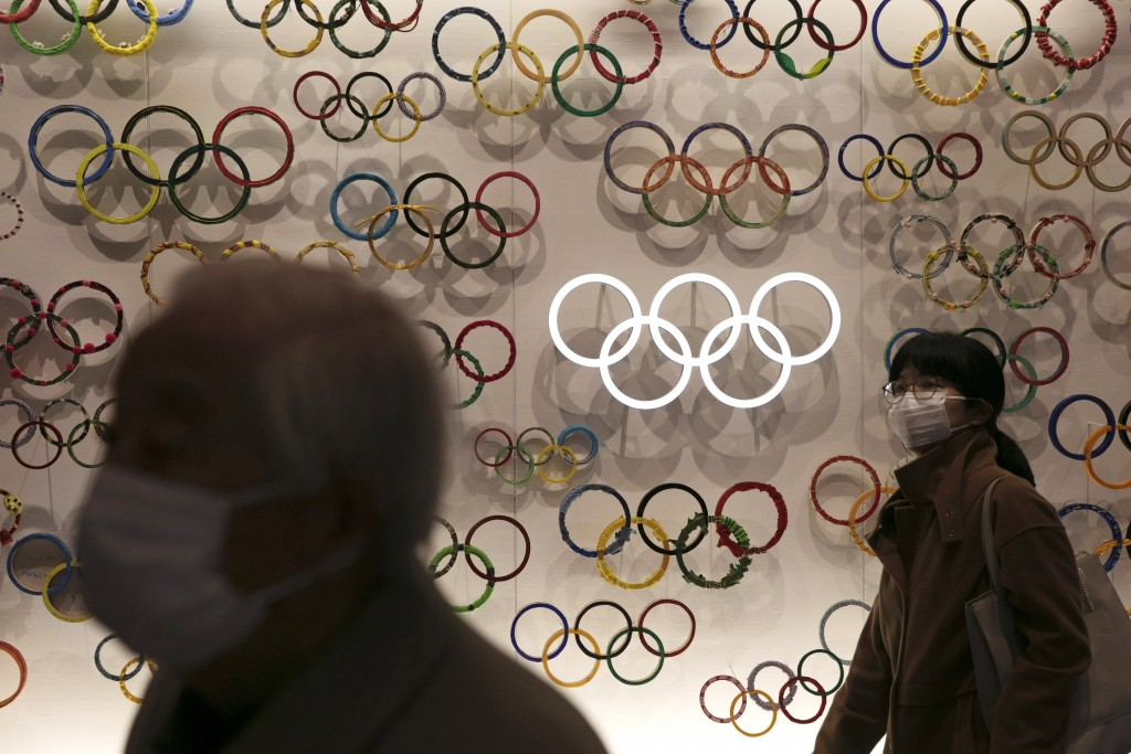 FILE - In this Feb. 23, 2020, file photo, two people wear masks as they visit the newly opened Japan Olympic Museum located near the New National Stad...