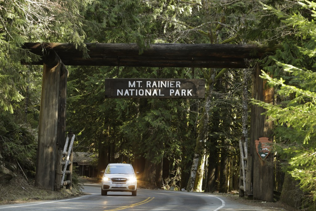 A car passes through the entrance to Mount Rainier National Park, Wednesday, March 18, 2020, in Washington state. Most national parks are remaining op...