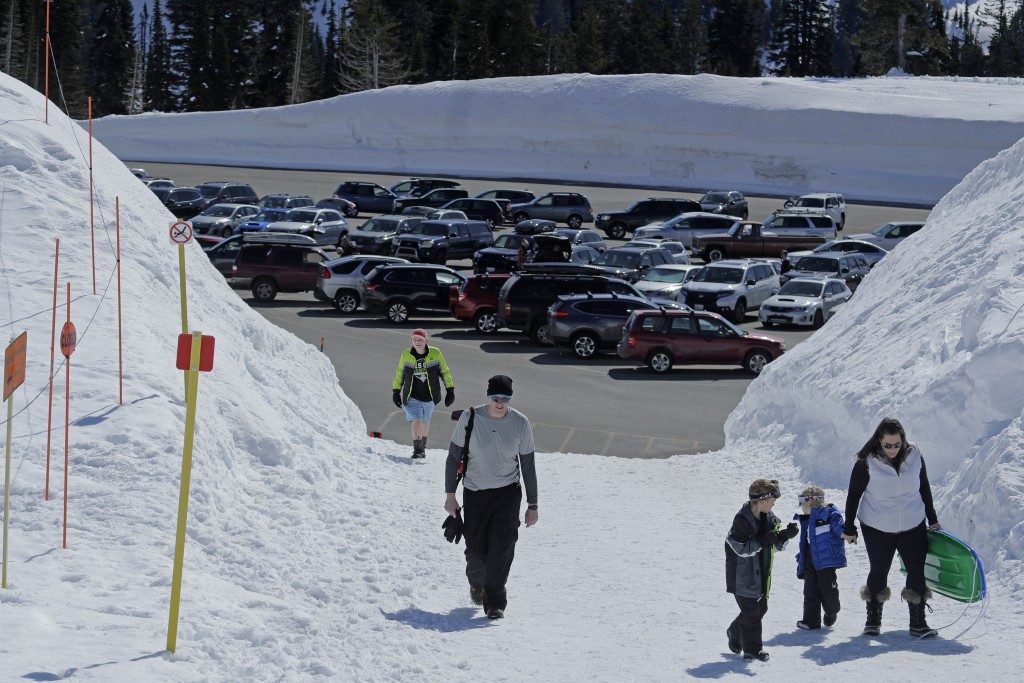 Visitors to Mount Rainier National Park walk toward the sledding area at Paradise, Wednesday, March 18, 2020, in Washington state. Most national parks...