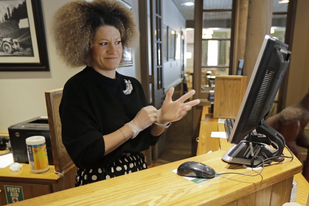 Evelyn Waruszewski puts on gloves as she works at a reception desk at the National Park Inn at Longmire at Mount Rainier National Park, Wednesday, Mar...