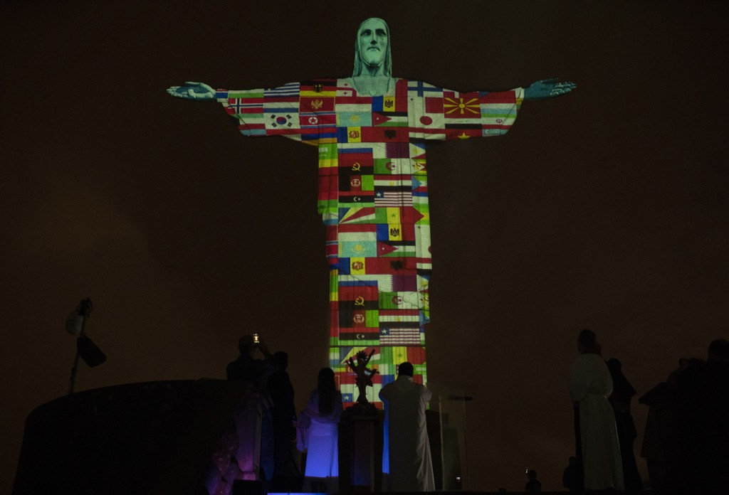 Rio's Christ the Redeemer statue is lit up with the flags of countries currently afflicted by the new coronavirus in Rio de Janeiro, Brazil, Wednesday...