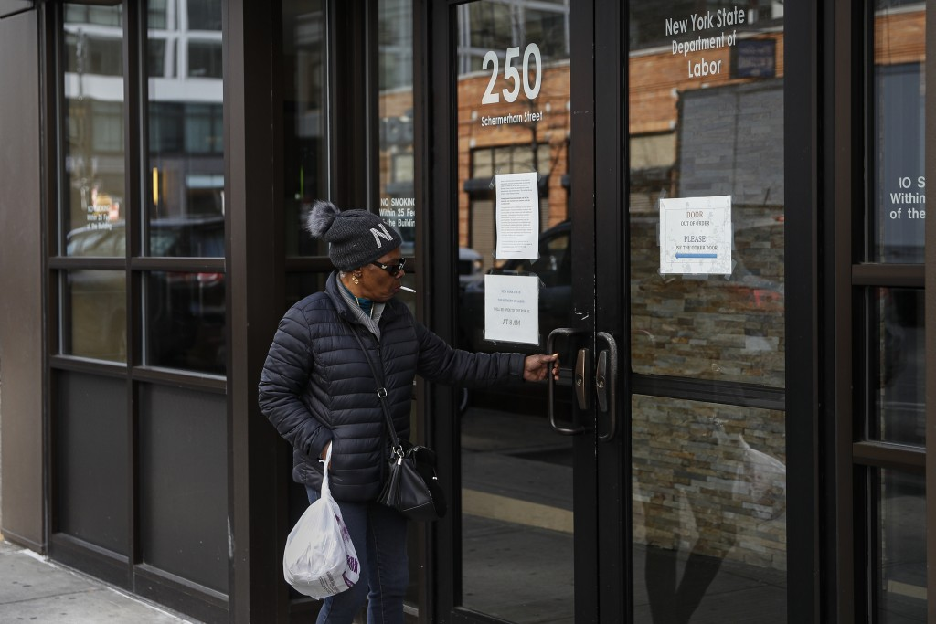 Visitors are unable to gain access to the Department of Labor due to closures over coronavirus concerns, Wednesday, March 18, 2020, in New York. Appli...