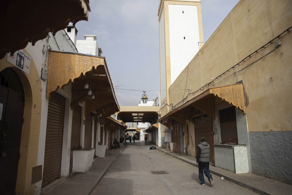 A man walks next to closed shops in the usually-bustling Medina of Rabat, on the day Moroccan authorities called on citizens to limit their movements ...