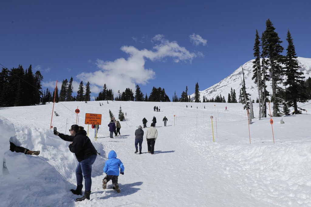Visitors to Mount Rainier National Park walk toward the sledding area at Paradise on Wednesday, March 18, 2020, in Washington state. Most national par...