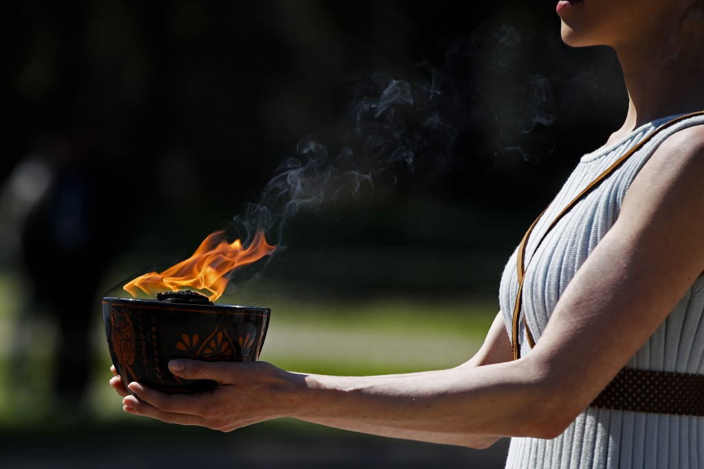 FILE - In this March 12, 2020, file photo, an actress, playing the role of the priestess, holds the flame during the flame lighting ceremony at the cl...