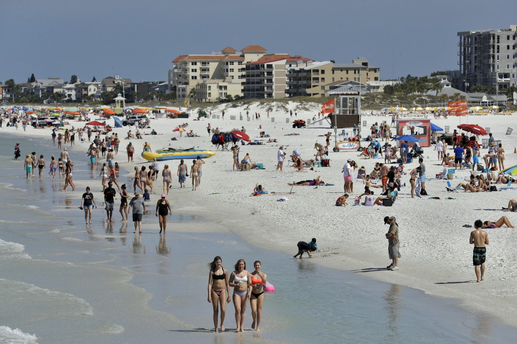 Visitors enjoy Clearwater Beach, Wednesday, March 18, 2020, in Clearwater Beach, Fla. Beach goers are keeping a safe distance from each other to help ...