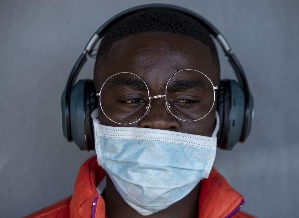 A barber wearing wearing a surgical mask at a hair salon in Soweto, South Africa, Thursday, March 19, 2020. For most people the virus causes only mild...