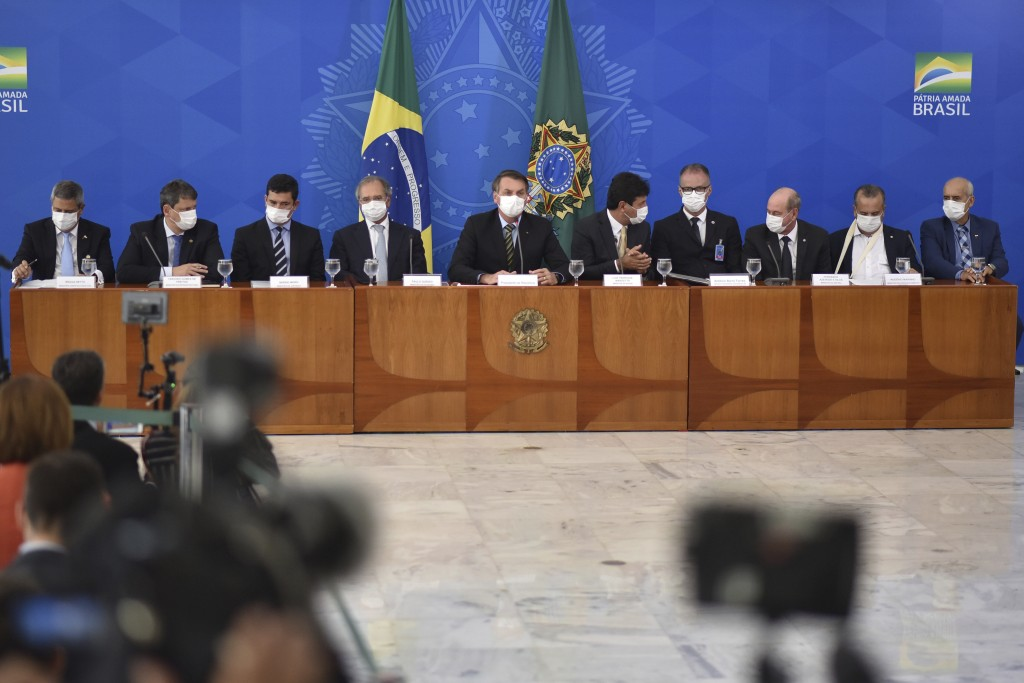 Brazil's President Jair Bolsonaro, center, accompanied by his ministers all wearing masks, speaks during a press conference on the new coronavirus, at...