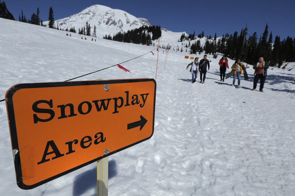 Visitors to Mount Rainier National Park walk away from the sledding area at Paradise, Wednesday, March 18, 2020, in Washington state. Most national pa...