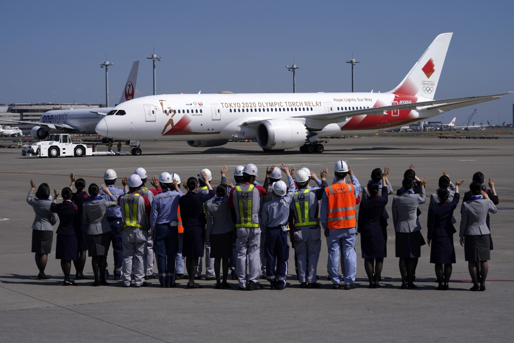 """FIEL - In this March 18, 2020, file photo, ground crews of Japanese airlines wave to the special """"Tokyo 2020 Go"""" aircraft that will transport the Olym..."""