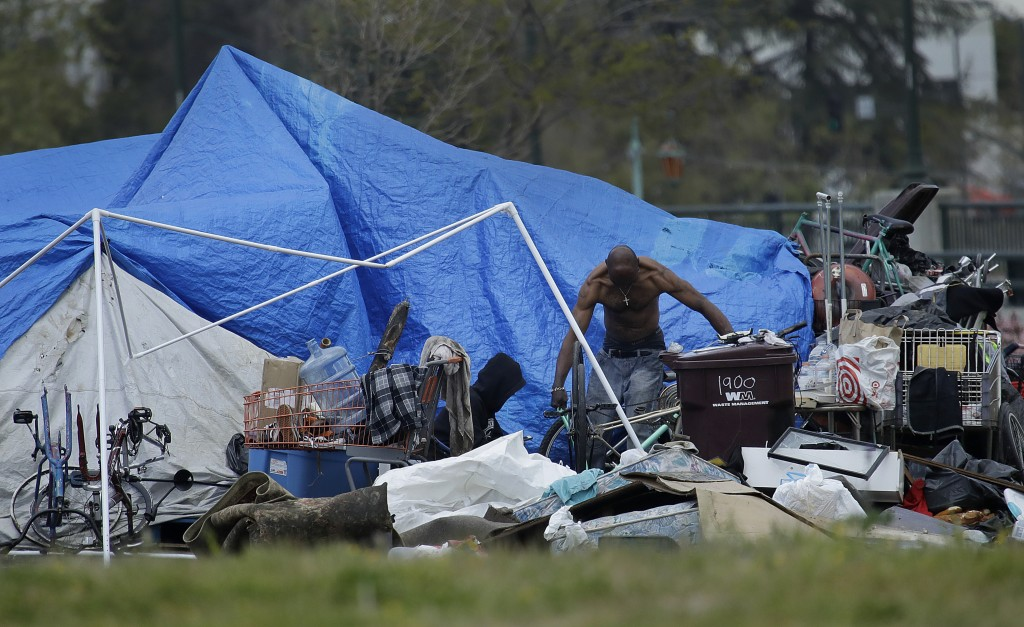 A man is seen in a homeless encampment on Thursday, March 19, 2020, in Oakland, Calif. California governor Gavin Newsom has authorized $150 million in...