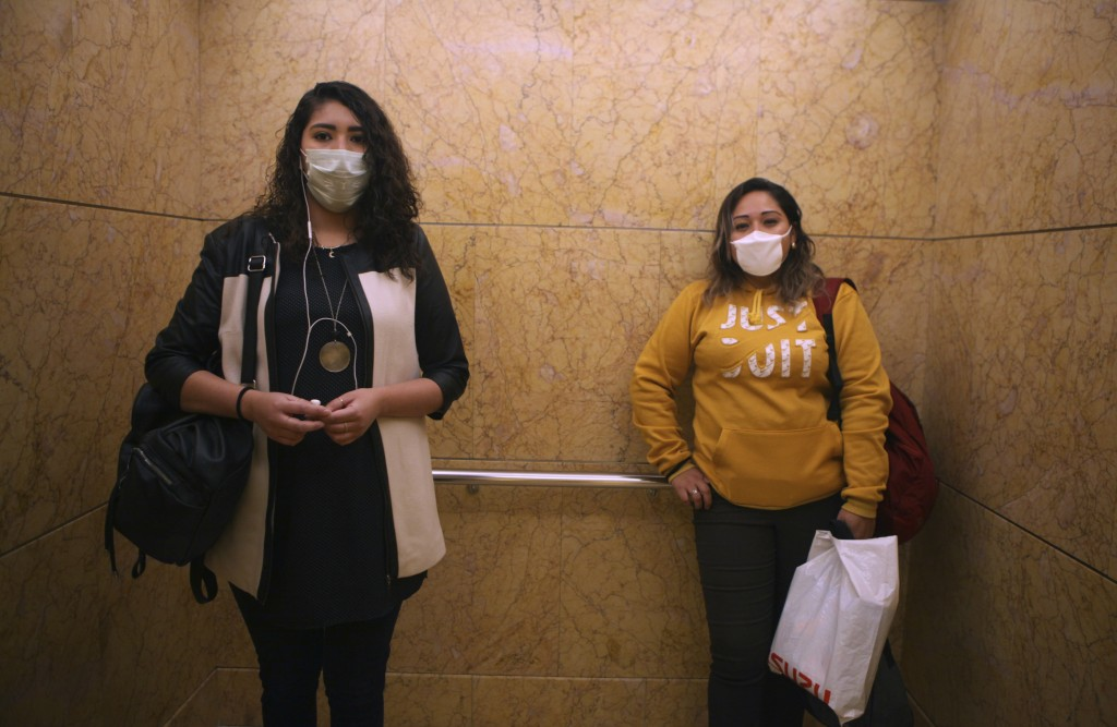 Women wear face masks as a precaution against the spread of the new coronavirus as they ride the elevator to their offices in Mexico City, Thursday, M...