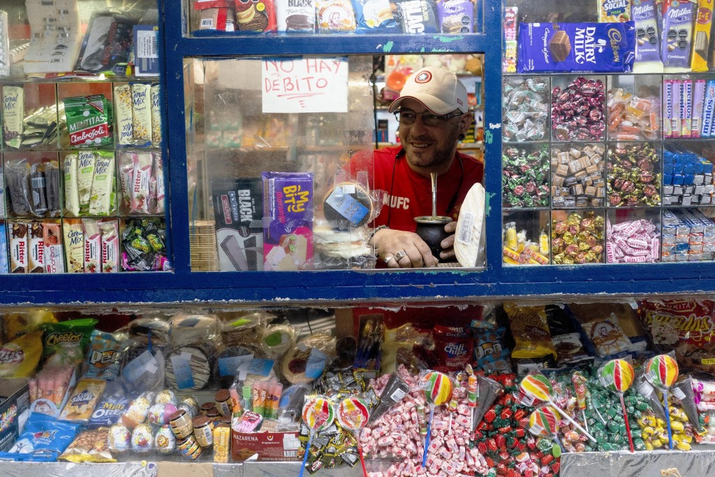 "In this March 18, 2020 photo, Ivan holds his ""mate"" inside a candy kiosk as he works in Montevideo, Uruguay. Not withstanding the new coronavirus emer..."