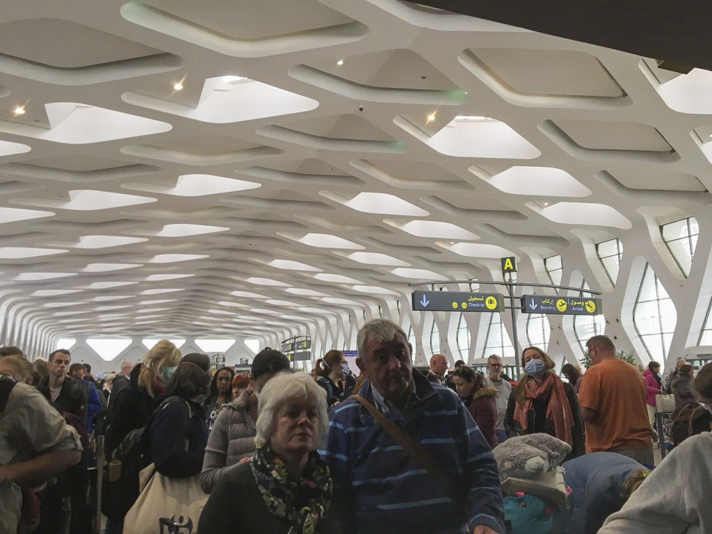 Passengers line up to board one of the few flights out of Morocco, in Marrakech, Thursday, March 19, 2020. Morocco suspended all international passeng...