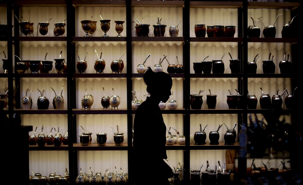 "In this March 17, 2020 photo, Paola Garcia walks past herbal ""mate"" mugs at the shop where she works in Buenos Aires, Argentina, Tuesday, March 17, 20..."