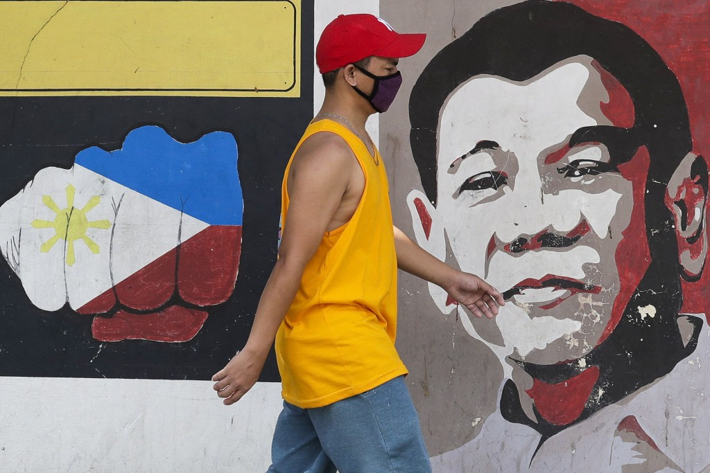 A man wearing a protective mask walks past an image of Philippine President Rodrigo Duterte in Manila, Philippines on Friday March 20, 2020. The Phili...