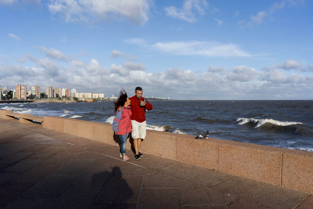 "In this March 19, 2020 photo, Marina and Fabio walk arm and arm by the seaside as they drink ""mate"" in Montevideo, Uruguay. In Uruguay, Paraguay and A..."