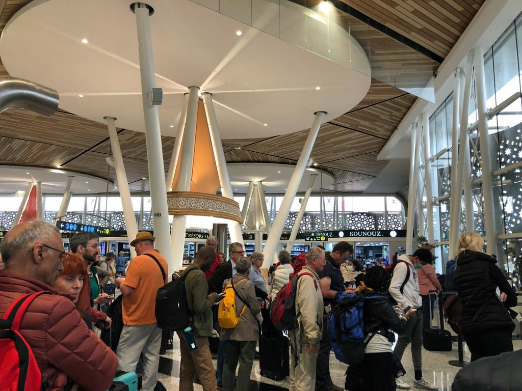 Passengers line up to board one of the few flights out of Morocco in Marrakech, Thursday, March 19, 2020. Morocco suspended all international passenge...